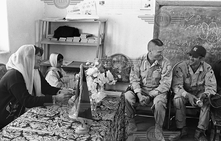 American commander Lieutenant Colonel Stammer of the US Army and his interpreter talks with the headmistress of a local primary school, near where the army has a military base.....