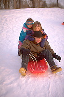 Cousins ages 22 through 5 sledding at Town and Country Golf Course. St Paul Minnesota USA