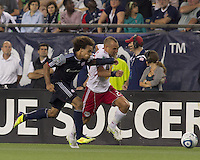 New York Red Bulls midfielder Joel Lindpere (20) dribbles down the wing as New England Revolution defender Kevin Alston (30) defends. In a Major League Soccer (MLS) match, the New England Revolution tied New York Red Bulls, 2-2, at Gillette Stadium on August 20, 2011.