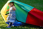 Lucy Diamond, 1, of  Manchester, runs under a Childs multi-color parachute, during a play area near the concert series taking place nearby, at Center Memorial Park, August 15, 2019, in Manchester. (Jim Michaud / Journal Inquirer)