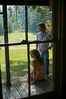 Young couple together on porch seen through window
