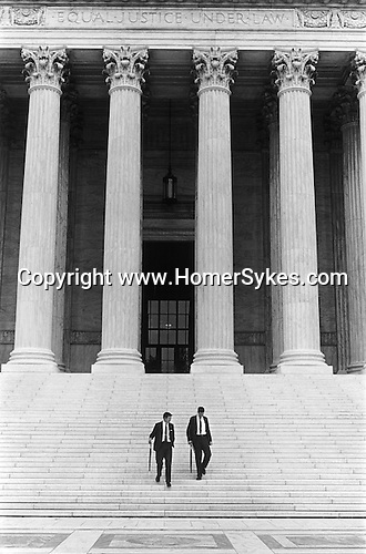 "WASHINGTON DC - USA 1969 EQUAL JUSTICE UNDER LAW. TWO IDENTICALLY DRESSED MEN IN BUSINESS SUITS AND CARRYING ROLLED UMBRELLAS WALK DOWN  ""Equal justice under law"" is a phrase engraved on the front of the United States Supreme Court building in Washington"
