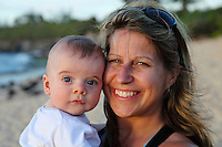 A smiling mother and her baby son at Ho'okipa Beach Park, Maui.