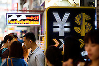 HONG KONG, MAY 08: People pass by a currency exchange booth showing symbols of different currencies including Hong Kong dollar and Chinese yuan (RMB), on May 8, 2015, in Hong Kong. (Photo by Lucas Schifres/Pictobank)