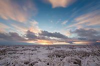 Sun sets over the snow covered tundra of the Arctic North Slope, Alaska.