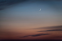 A tiny sliver of crescent moon hovers over and between clouds at sunset.  San Leandro Marina on San Francisco Bay.