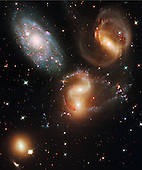 Washington, DC - September 9, 2009 -- A clash among members of a famous galaxy quintet reveals an assortment of stars across a wide color range, from young, blue stars to aging, red stars.  This portrait of Stephan's Quintet, also known as Hickson Compact Group 92, was taken by the new Wide Field Camera 3 (WFC3) aboard the National Aeronautics and Space Administration's (NASA) Hubble Space Telescope. Stephan's Quintet, as the name implies, is a group of five galaxies. The name, however, is a bit of a misnomer. Studies have shown that group member NGC 7320, at upper left, is actually a foreground galaxy about seven times closer to Earth than the rest of the group.  Three of the galaxies have distorted shapes, elongated spiral arms, and long, gaseous tidal tails containing myriad star clusters, proof of their close encounters. These interactions have sparked a frenzy of star birth in the central pair of galaxies. This drama is being played out against a rich backdrop of faraway galaxies.  The image, taken in visible and infrared light, showcases WFC3's broad wavelength range. The colors trace the ages of the stellar populations, showing that star birth occurred at different epochs, stretching over hundreds of millions of years. The camera's infrared vision also peers through curtains of dust to see groupings of stars that cannot be seen in visible light.  NGC 7319, at top right, is a barred spiral with distinct spiral arms that follow nearly 180 degrees back to the bar. The blue specks in the spiral arm at the top of NGC 7319 and the red dots just above and to the right of the core are clusters of many thousands of stars. Most of the quintet is too far away even for Hubble to resolve individual stars.  Continuing clockwise, the next galaxy appears to have two cores, but it is actually two galaxies, NGC 7318A and NGC 7318B. Encircling the galaxies are young, bright blue star clusters and pinkish clouds of glowing hydrogen where infant stars are being born. These stars