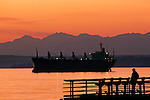 Silhouetted pier with man fishing off pier at sunset on Puget sound with Olympic mountains Seattle Washington State USA
