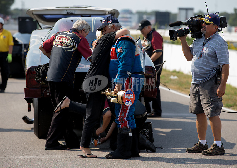 Aug. 18, 2013; Brainerd, MN, USA: NHRA top alcohol funny car driver Frank Manzo celebrates with his wife after winning the Lucas Oil Nationals at Brainerd International Raceway. Mandatory Credit: Mark J. Rebilas-