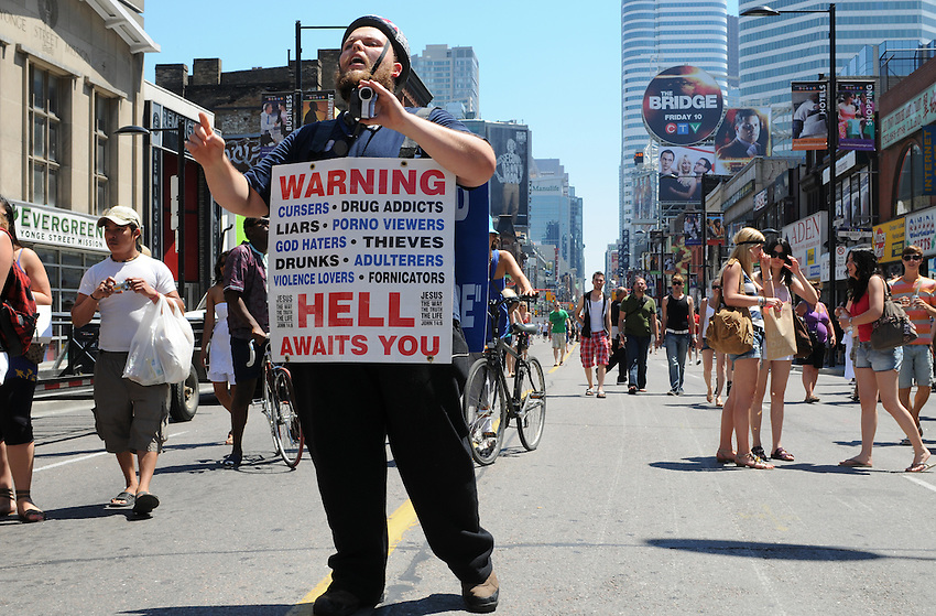 Candid Street Portrait of a lonely dissenter, taken just before Toronto's 2010 Pride Parade, a signaure event in a city rich with culture.