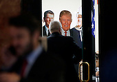 A man enters a room decorated with a Ronald Regan, Donald Trump and John Wayne cardboard cutout / posters in Trump Tower on January 11, 2017 in New York City. U.S. President Elect Donald Trump is still holding meetings upstairs at Trump Tower as he continues to fill in key positions in his new administration.    <br /> Credit: John Angelillo / Pool via CNP