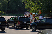 Protestors stand at the curb with signs against United States President Donald J. Trump as his motorcade departs the Trump National Golf Club in Sterling, Virginia on September 2, 2018.    <br /> Credit: Ken Cedeno / Pool via CNP
