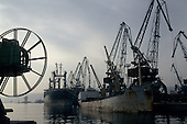 Port of Varna, Bulgaria. Ships docked with dockside cranes; double wheel in the foreground.