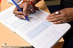 Education preschool 4 year olds closeup of female teacher's hands marking the attendance roll book horizontal
