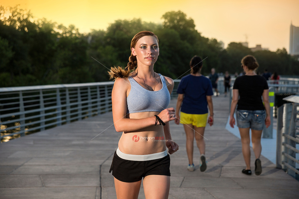 Attractive fit female runner runs on the The Boardwalk Trail along Lady Bird Lake in downtown Austin, Texas