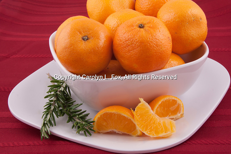 oranges lay in a bowl on a red tablecloth.