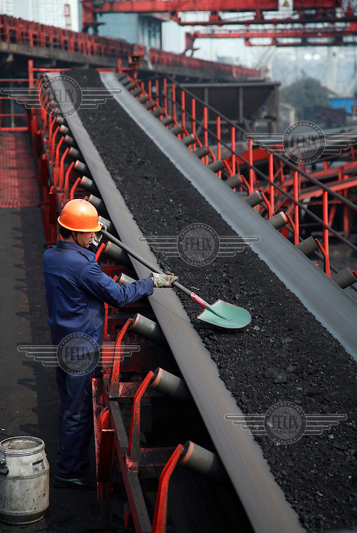 A worker takes samples of coal for quality tests from a conveyor belt at a coal depot in Shanghai.