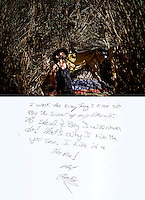 """This is a scan of a print that was given to the subject, Tim 'Timbow' Bowman, so that he could write his thoughts. He wrote:..""""I work for everything I ever get By the sweat of my Brow. To steal & Beg I will never do! That's why I live here you see. I live in a Tee Pee! TimBow""""..Caption for the photo:.Ventura, California, July 23, 2010 - A portrait of Tim 'Timbow' Bowman in front of his tent that is hidden by the 16-foot tall grass and bamboo on the Ventura River bottom. Bowman has been homeless and living along the river since the early 1990's.  In 1987 his 18-month-old daughter, Miranda Laurel, died from Lyme disease. His wife left him soon afterwards. A year later he fell through a plate glass window while working on a construction site, leaving him disabled and unable to work construction. He says the loss of his wife and daughter and his struggles with work sent him into a spiral. He eventually lost his home. He says he lives in the 300+ community along the river bottom because he """"feels at home."""" Adding, """"I feel loved down here. Up there is nothing but trouble."""" The two-mile stretch of river bottom from the Pacific to Stanley Road is home to about 300 homeless, who have carved tunnels and paths into the tall grass and bamboo. Bowman, who survives off of SSI, says, """"I lead an honest life. I don't steal, I don't rob and I share whatever I can."""" .."""