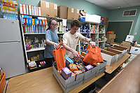 Cecelia Johnson (left) and Russ Johnson, both of Fayetteville, pack food boxes Monday March 16, 2020 at the Fayetteville Public Schools food pantry called The Outback. Anyone who needs food can come by the location from 1:00 A.M. to 1:00 P.M. this week at the ALLPS School of Innovation at 2350 Old Farmington Rd. In Fayetteville. Visit nwaonline.com/200317Daily/ for more images. (NWA Democrat-Gazette/J.T. Wampler)