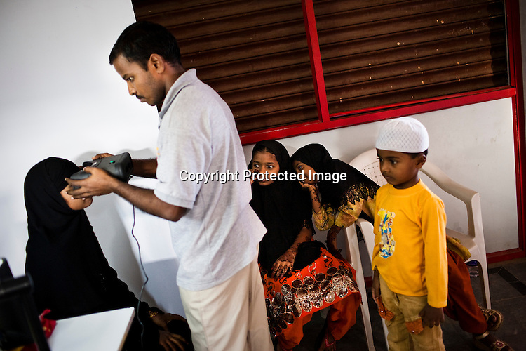 Sheikh Mohammadie Begum's children (right) are seen amused by seeing her iris scan on the monitor as part of the enrollment that is on its way in Naagaaram village, outskirts of Hyderabad in Andhra Pradesh, India. India is assigning each one of its 1.2 billion people a unique ID number based on digital finger prints and iris scan. Photograph: Sanjit Das/Panos