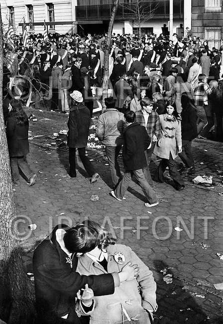 Manhattan, New York City, NY. March 17th, 1970.<br /> &quot;Kiss me: I am Irish&quot;. A couple kissing next to a tree away from the crowd during St. Patrick's Day Parade on 5th Ave. at 96th