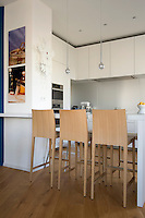 A row of wooden bar stools lines the breakfast bar in this contemporary kitchen