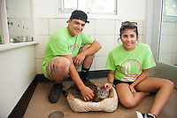 Salve Regina Freshmen Jared Tirocchi and Leah Rainbow spend time with Lillian, one of many animals for adoption at the Potter League For Animals, as they begin their community service project.