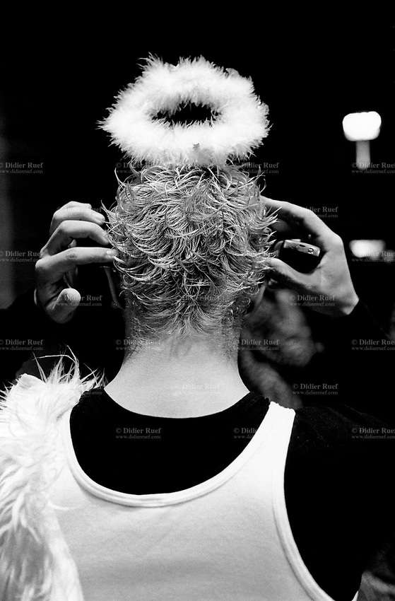 Switzerland. Canton Ticino. Bellinzona. Carnival. Back of a young man, dressed up as an angel. He holds both hands on both ears. Mobile phone in the right hand. © 2007 Didier Ruef