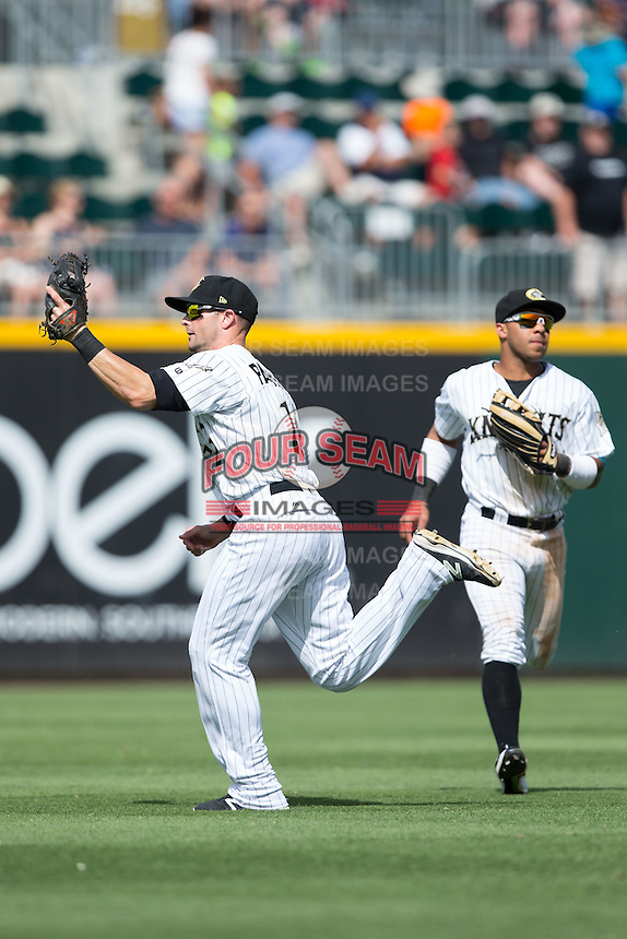 Charlotte Knights shortstop Andy Parrino (12) makes a running catch of a fly ball in front of left fielder Leury Garcia (24) during the game against the Indianapolis Indians at BB&T BallPark on June 19, 2016 in Charlotte, North Carolina.  The Indians defeated the Knights 6-3.  (Brian Westerholt/Four Seam Images)