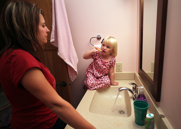 Ella Jacobs, 3, brushes her teeth with her mother, Heather, in their Polk City home.  Heather lost her husband, Eric, in a plane crash in 2006 when she was eight months pregnant with their youngest, Ella, and has since been raising her five young children on her own.