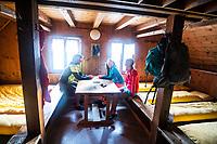 Friends sit around in a sleeping room of the Turtmann Hut during the Via Valais, a multi-day trail running tour connecting Verbier with Zermatt, Switzerland.
