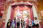 Young visitors pose for a photo with staff dressed in Hello Kitty and Hello Melody costumes at the opening of Hello Kitty's Kawaii (Cute) Paradise, a Hello Kitty theme store, in Tokyo, Japan on Thursday 21 October  2010. .Photographer: Robert Gilhooly
