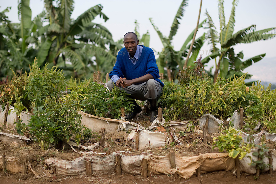 "May0016089 . Daily Telegraph..Features..Gad, manager of Murangi training farm in the Rusizi district of southern Rwanda sitting on a terraced ""kitchen garden"". The farm has been built by Rwanda Aid a British charity and recipient of funds from the Daily Telegraph's 2005 Christmas appeal...Rwanda was the scene of a brutal civil and genocide which ended in 1994 leaving behind 800,000 dead, hundreds of thousands of refugees, many orphans suffering with mental trauma . Still recovering from the civil war the small,landlocked central African state is one of the poorest countries in the world with three quarters of it's 10 million population living below the poverty line and is a huge recipient of foreign aid....Rwanda 28 August 2009"