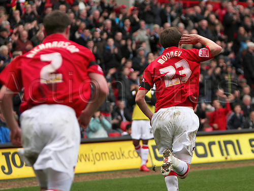 """20/03/2010. David Mooney (23) celebrates scoring the second goal for Charlton by taunting the Gillingham fans with a """"Can't Hear You"""" gesture - Frazer Richardson rushes over to congratulate him. Division 1 match - Charlton Athletic v Gillingham, London / Kent, England, UK."""
