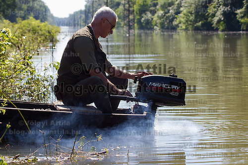Man starts a motorboat during the flooding in the forest in Gemenc (about 218 km South of the capital city Budapest), Hungary on June 14, 2013. ATTILA VOLGYI
