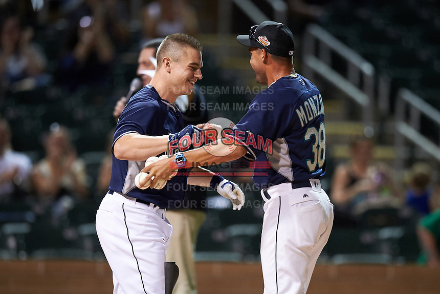 Peoria Javelinas Tyler O'Neill (11), of the Seattle Mariners organization, is congratulated by coach  Yoel Monzon (38) after becoming the first participant in history to hit a home run off a batting tee during the Bowman Hitting Challenge on October 8, 2016 at the Salt River Fields at Talking Stick in Scottsdale, Arizona.  (Mike Janes/Four Seam Images)