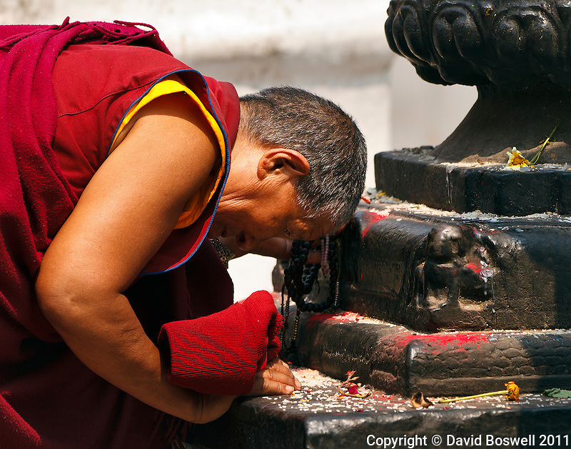 A Buddhist monk shows his devotion at the Boudhanath Stupa in Kathmandu, nepal.