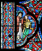 A female saint and a woman to the left of the scene of the apostles at the deathbed of Mary, The Death of the Virgin, from the Glorification of the Virgin stained glass window, in the nave of Chartres Cathedral, Eure-et-Loir, France. This window depicts the end of the Virgin's life on earth, her dormition and assumption, as told in the apocryphal text the Golden Legend of 1260. Chartres cathedral was built 1194-1250 and is a fine example of Gothic architecture. Most of its windows date from 1205-40 although a few earlier 12th century examples are also intact. It was declared a UNESCO World Heritage Site in 1979. Picture by Manuel Cohen