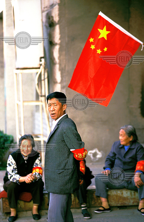 Mark Henley/Panos Pictures..China, Beijing..Good socialist citizens. Volenteer security to survey the rest, during official celebrations.