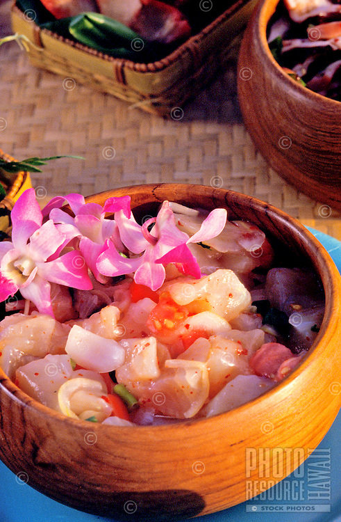 """Island style """"""""poke,"""""""" seasoned raw fish in a wooden bowl with an orchid garnish"""
