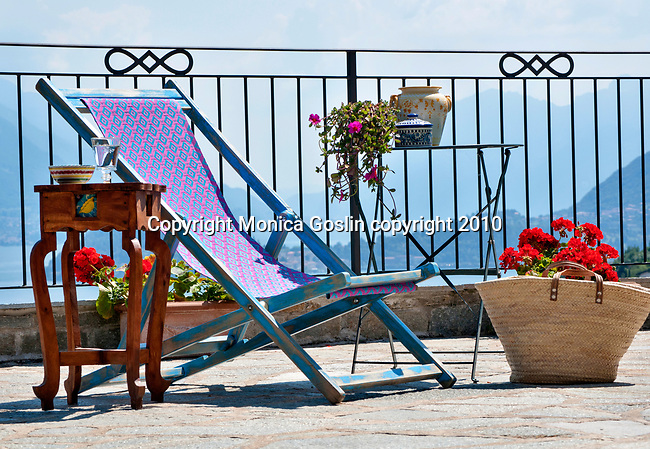 A terrace in Menaggio with a small wooden table, blue and pink chair, and straw basket with a view of Lake Como, Italy and Bellagio in the background