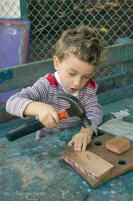 "Berkeley CA Boy, four-years-old experimenting with carpentry at local ""discovery park"" for free-form activities  MR"