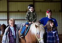 NWA Democrat-Gazette/JASON IVESTER<br /> Volunteers help as Caleb Burton, Northside Elementary third-grader, rides a horse in the arena Tuesday, May 2, 2017, during the Special Olympics equestrian event at Horses for Healing in Bentonville. Thirty students from Rogers schools participated in the theraputic riding event.