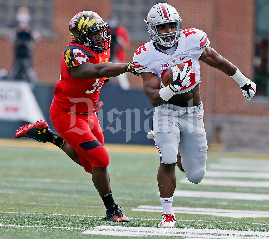 Ohio State Buckeyes running back Ezekiel Elliott (15) carries the ball pursued by Maryland Terrapins linebacker L.A. Goree (53) in the first quarter of their game at Byrd Stadium in College Park, Maryland on October 4, 2014. (Columbus Dispatch photo by Brooke LaValley)