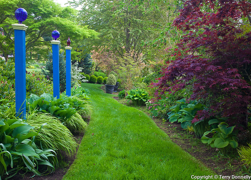 Vashon Island, Washington<br /> Garden detail of a grassy path guided with blue posts