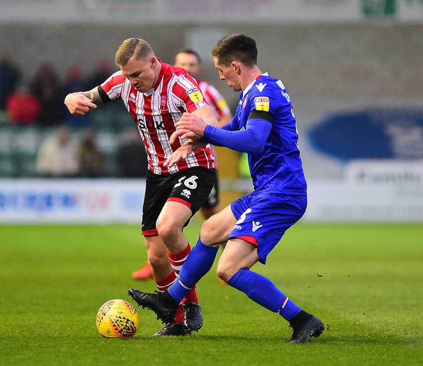 Lincoln City's Harry Anderson battles with Morecambe's Luke Conlan<br /> <br /> Photographer Andrew Vaughan/CameraSport<br /> <br /> The EFL Sky Bet League Two - Saturday 15th December 2018 - Lincoln City v Morecambe - Sincil Bank - Lincoln<br /> <br /> World Copyright © 2018 CameraSport. All rights reserved. 43 Linden Ave. Countesthorpe. Leicester. England. LE8 5PG - Tel: +44 (0) 116 277 4147 - admin@camerasport.com - www.camerasport.com