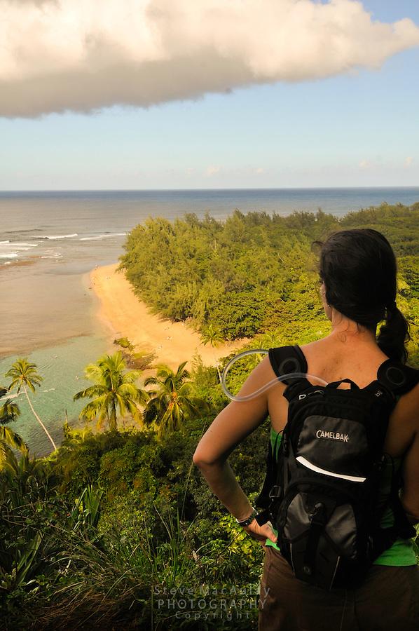 Female hiker checking out the view of Ke'e Beach from Kalalalau Trail, Northshore, Kauai, Hawaii