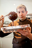 Chocolatier Patrice Arbona fills moulds with chocolate at 'Entre Mes Chocolats', Vence, France, 10 February 2011