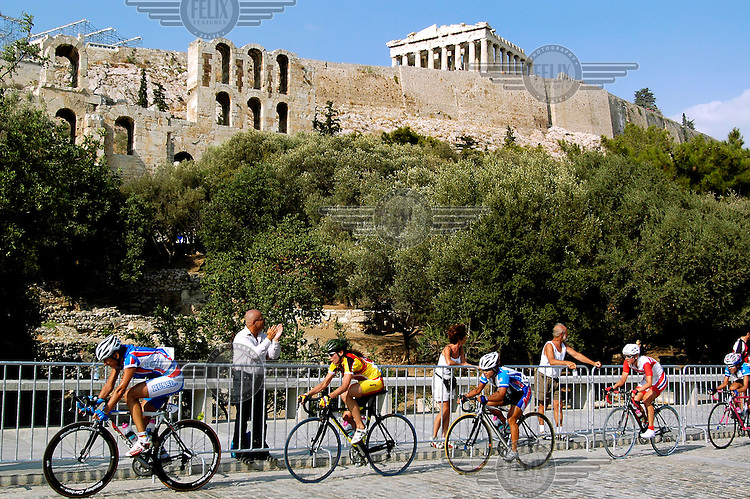 Competitors in the Women's Road Race at the XXVIII Olympiad cycle up Dionissiou Aeropagitou Street passing beneath the Acropolis.