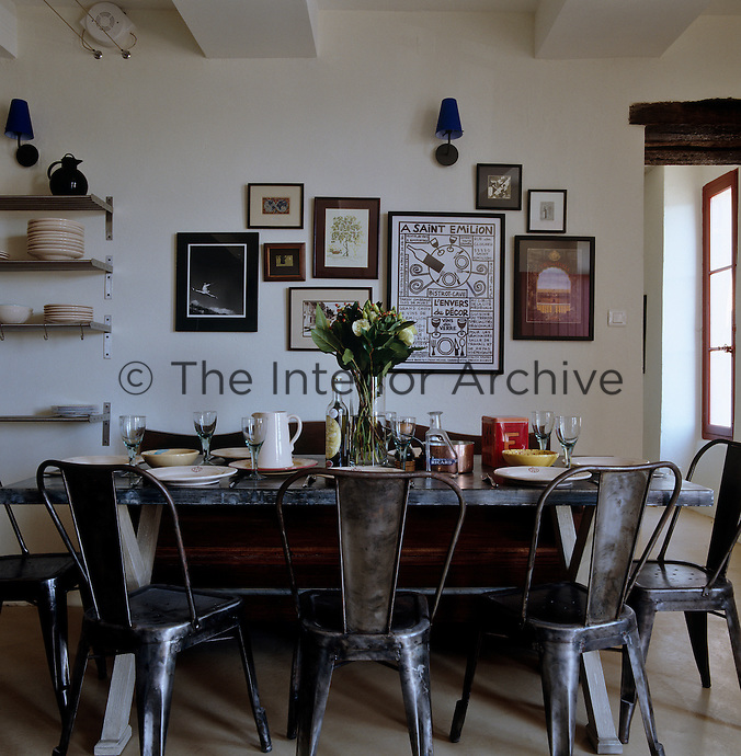A zinc-topped table surrounded by metal chairs and an old wooden bench is set for an informal lunch